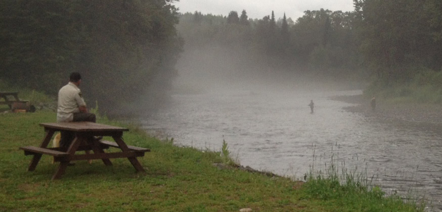 An NB Warden eyes the angling action at Kedgwick Forks this summer. Photo Geoff Giffin/ASF