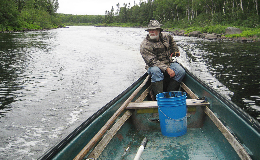Dave Vardy motoring through Dark Angle Pool on the Gander River in a Gander River boat in late July, 2013.